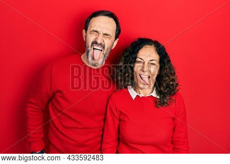 Middle age couple of hispanic woman and man hugging and standing together sticking tongue out happy with funny expression. emotion concept.
