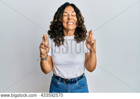 Middle age hispanic woman wearing casual white t shirt gesturing finger crossed smiling with hope and eyes closed. luck and superstitious concept.
