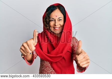Middle age hispanic woman wearing tradition sherwani saree clothes approving doing positive gesture with hand, thumbs up smiling and happy for success. winner gesture.