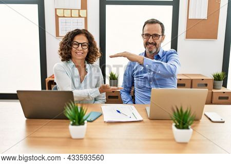 Middle age hispanic woman and man sitting with laptop at the office gesturing with hands showing big and large size sign, measure symbol. smiling looking at the camera. measuring concept.