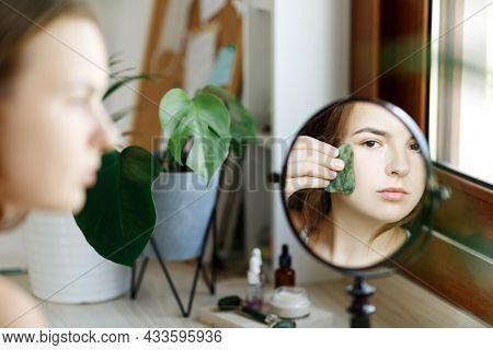 Close Up Portrait Of Adult Caucasian Woman, Using Natural Gua Sha Jade Stone Roller To Massage Face