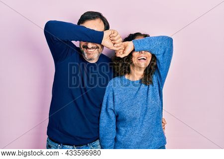 Middle age couple of hispanic woman and man hugging and standing together smiling cheerful playing peek a boo with hands showing face. surprised and exited