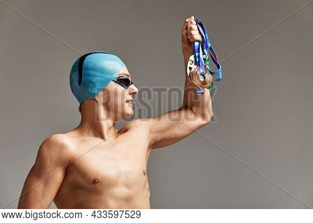 Swimmer With A Medal On A Gray Background Rejoices In Victory, An Athlete In Excellent Physical Shap