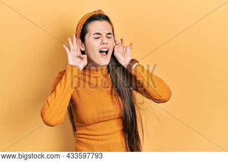 Young brunette teenager wearing casual yellow sweater trying to hear both hands on ear gesture, curious for gossip. hearing problem, deaf