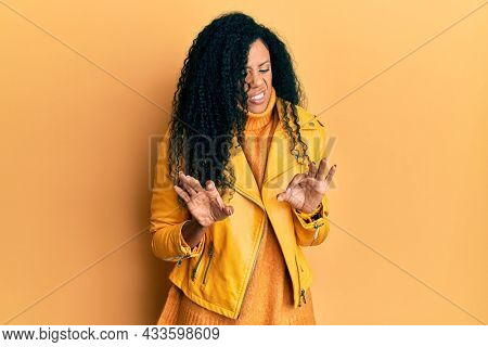 Middle age african american woman wearing wool winter sweater and leather jacket disgusted expression, displeased and fearful doing disgust face because aversion reaction.