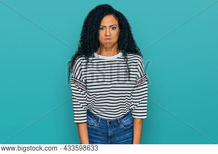Middle age african american woman wearing casual clothes puffing cheeks with funny face. mouth inflated with air, crazy expression.