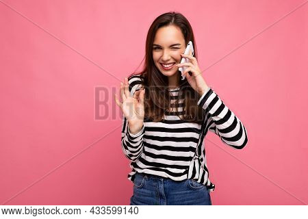 Winking Pretty Happy Young Woman Speaking On The Phone Wearing Striped Sweater Isolated Over Backgro