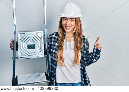 Young caucasian woman wearing hardhat holding ladder surprised with an idea or question pointing finger with happy face, number one