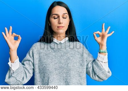 Young hispanic woman wearing casual clothes relaxed and smiling with eyes closed doing meditation gesture with fingers. yoga concept.