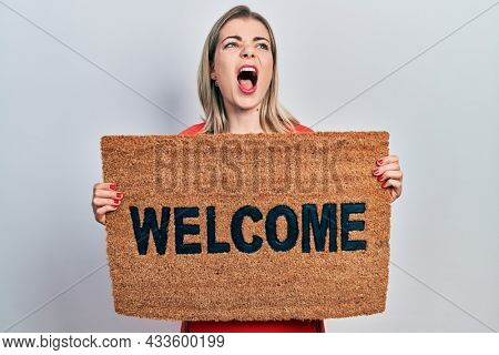 Beautiful caucasian woman holding welcome doormat angry and mad screaming frustrated and furious, shouting with anger looking up.