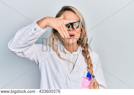 Beautiful young blonde woman wearing optometry glasses peeking in shock covering face and eyes with hand, looking through fingers afraid