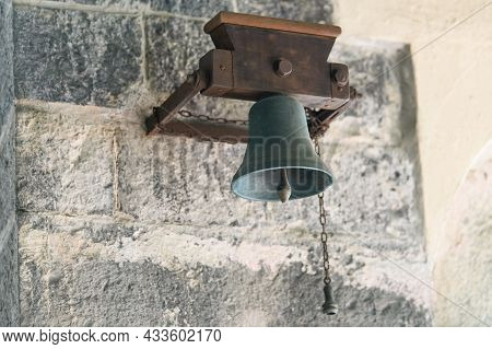 Old Bell Hanging On A Stone Wall