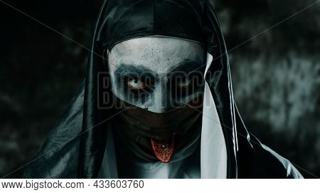 closeup of a scary evil nun, wearing a black and white habit, sticking out her pierced tongue through a hole in her black face mask