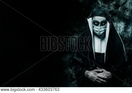 a scary evil nun, wearing a typical black and white habit and a disposable face mask, on a black background with some blank space on the left