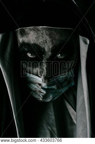 a scary evil nun, in a typical black and white habit, wears a dirty disposable face mask