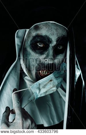a scary evil nun, in a black and white habit, is about to cover her mouth with bloody teeth, with a dirty disposable face mask