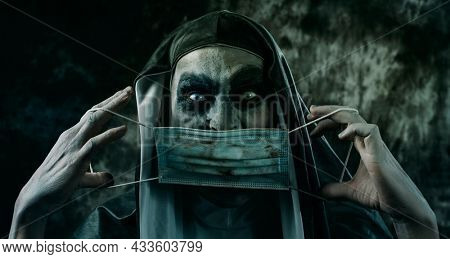 closeup of a scary evil nun, in a typical black and white habit, putting on or taking off a dirty disposable face mask