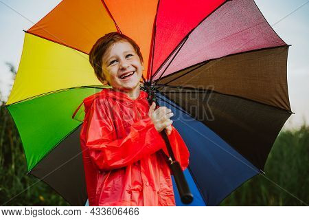 Portrait Of A Smiling School Boy With Rainbow Umbrella In The Park. Kid Holds Colourful Umbrella On