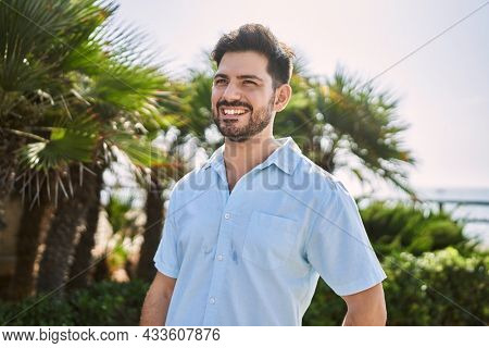 Young hispanic man smiling happy standing at the promenade