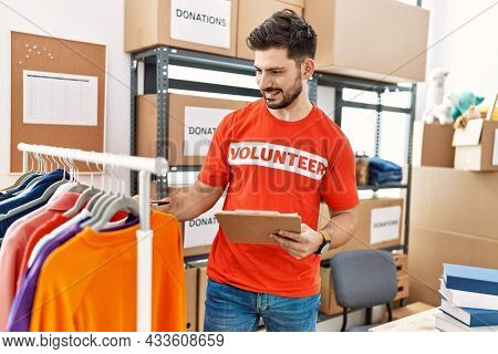 Young hispanic volunteer man holding clipboard working at charity center.