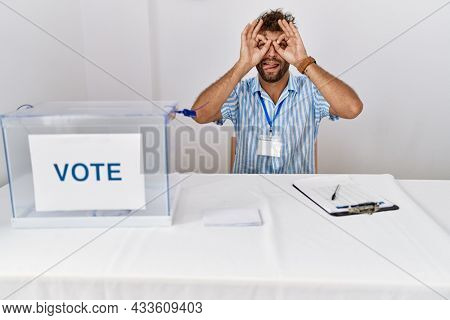 Young handsome man at political election sitting by ballot doing ok gesture like binoculars sticking tongue out, eyes looking through fingers. crazy expression.