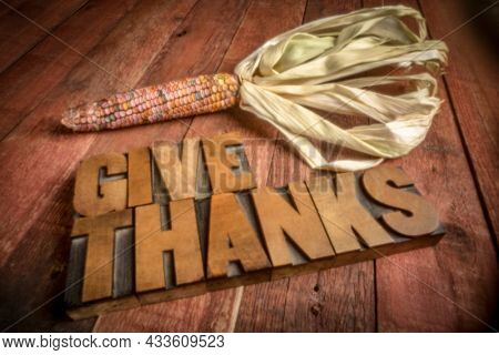 give thanks in vintage letterpress wood type with a decorative corn, soft focus image shot with a lensless pinhole camera, Thanksgiving theme