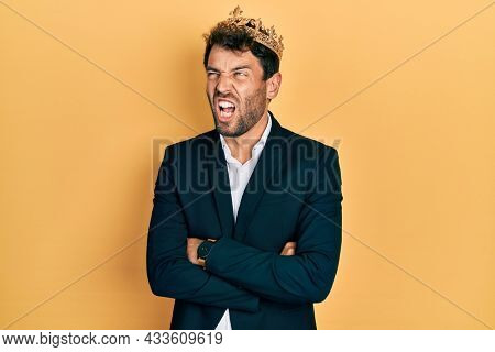 Handsome man with beard wearing business suit with arms crossed gesture and king crown angry and mad screaming frustrated and furious, shouting with anger. rage and aggressive concept.