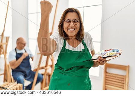 Middle age hispanic woman at art studio annoyed and frustrated shouting with anger, yelling crazy with anger and hand raised