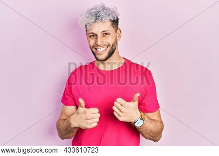 Young hispanic man with modern dyed hair wearing casual pink t shirt success sign doing positive gesture with hand, thumbs up smiling and happy. cheerful expression and winner gesture.