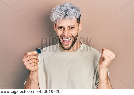 Young hispanic man with modern dyed hair holding sdxc card screaming proud, celebrating victory and success very excited with raised arms