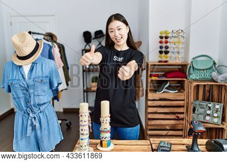 Young asian woman working as manager at retail boutique approving doing positive gesture with hand, thumbs up smiling and happy for success. winner gesture.
