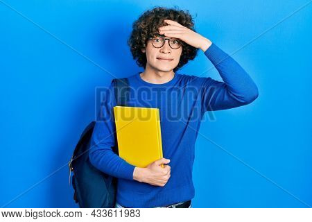 Handsome young man wearing student backpack and holding book stressed and frustrated with hand on head, surprised and angry face