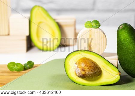 Halves Of Ripe Avocado And Micro Green On Wooden Podium And Stands Served On Table, White Background