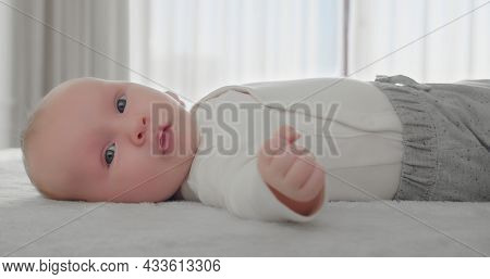 Portrait of a newborn baby looking at the camera. One-month-old baby is lying on his tummy in light clothes. White calm little boy looks at the camera. Close-up of a cute boy's face. Children concept.