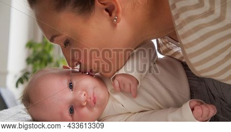 Happy Mother kissing her newborn baby. Closeup portrait of a loving mother's kiss.  Young mom kissing beautiful  infant child, at home. Mum loves of her infant son. Happy family. Parenthood concept.