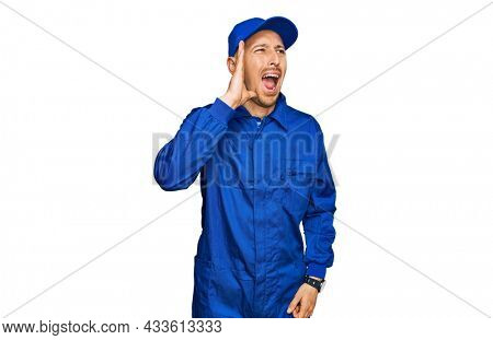 Bald man with beard wearing builder jumpsuit uniform shouting and screaming loud to side with hand on mouth. communication concept.