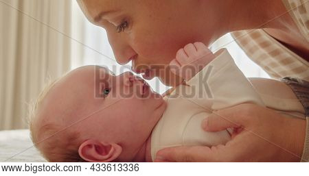 Adult Mother kissing her newborn son. Closeup portrait of a loving mother's kiss.  Young mom kissing beautiful  infant baby. Mum loves of her infant baby. Parenthood concept.