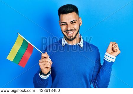 Young hispanic man with beard holding lithuania flag screaming proud, celebrating victory and success very excited with raised arm