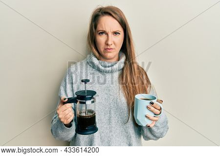 Young blonde woman drinking a cup of italian coffee skeptic and nervous, frowning upset because of problem. negative person.