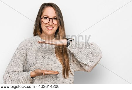 Young blonde woman wearing casual sweater and glasses gesturing with hands showing big and large size sign, measure symbol. smiling looking at the camera. measuring concept.