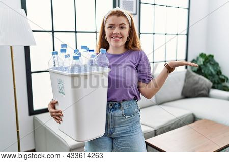 Young redhead woman holding recycling wastebasket with plastic bottles smiling cheerful presenting and pointing with palm of hand looking at the camera.