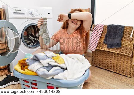 Young redhead woman putting dirty laundry into washing machine smiling cheerful playing peek a boo with hands showing face. surprised and exited
