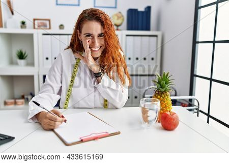 Young redhead woman nutritionist doctor at the clinic hand on mouth telling secret rumor, whispering malicious talk conversation