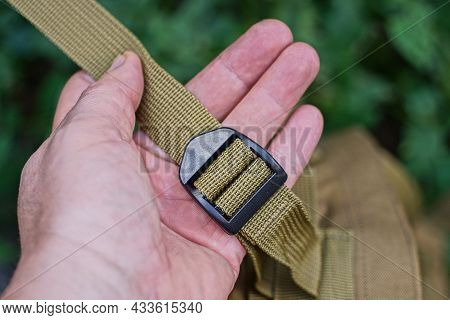 Hand Holds One Black Plastic Carabiner On The Long Green Harness Of The Backpack