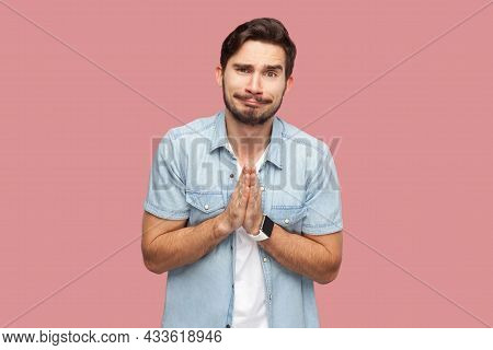 Please Help Me, Or Forgive. Portrait Of Sad Hopeful Handsome Bearded Young Man In Blue Casual Style