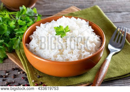 Cooked White Rice Garnished With Parsley In A Rustic Bowl (selective Focus, Focus On The Parsley And