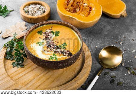 A Bowl Of Homemade Pumpkin Soup With Seeds, Sesame Seeds And Flax Seeds, Warm Autumn Food On The Tab
