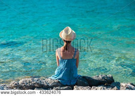 Little Girl In A Blue Summer Dress And A Straw Hat Sitting On A Rocky Shore Of The Sea - A Shot From