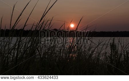 The Sun Sets Behinfd The Marsh Grasses At The Goose Creek Campground In Newpoet North Carolina,seaso
