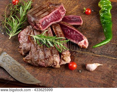 Roasted Piece Of Beef Ribeye Cut Into Pieces On A Vintage Brown Chopping Board, Rare Doneness. Delic